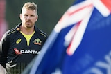 Aaron Finch stands with his hands behind his back in front of an Australian flag