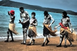 A group of boy walk along the beach dressed in traditional dress.