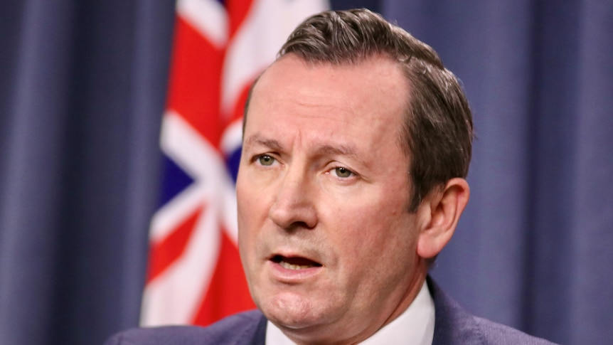 A close up of Mark McGowan wearing a suit, standing in front of a blue background and Australian flag.