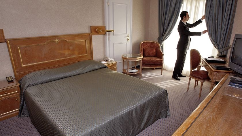Hotel staff member adjusts the curtain in a hotel room