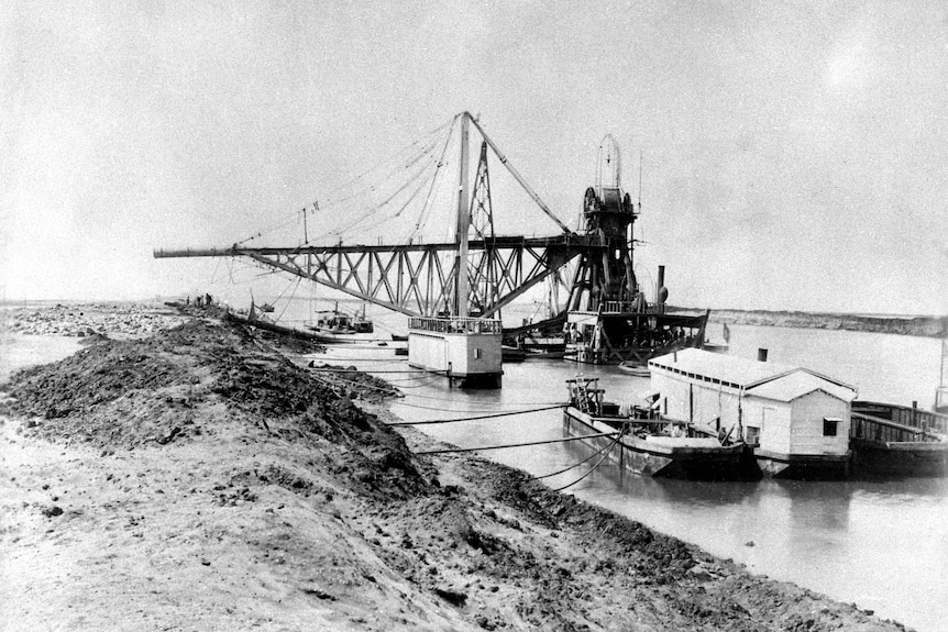 A large crane stands in the water near a wall of sand in a grainy black and white image.