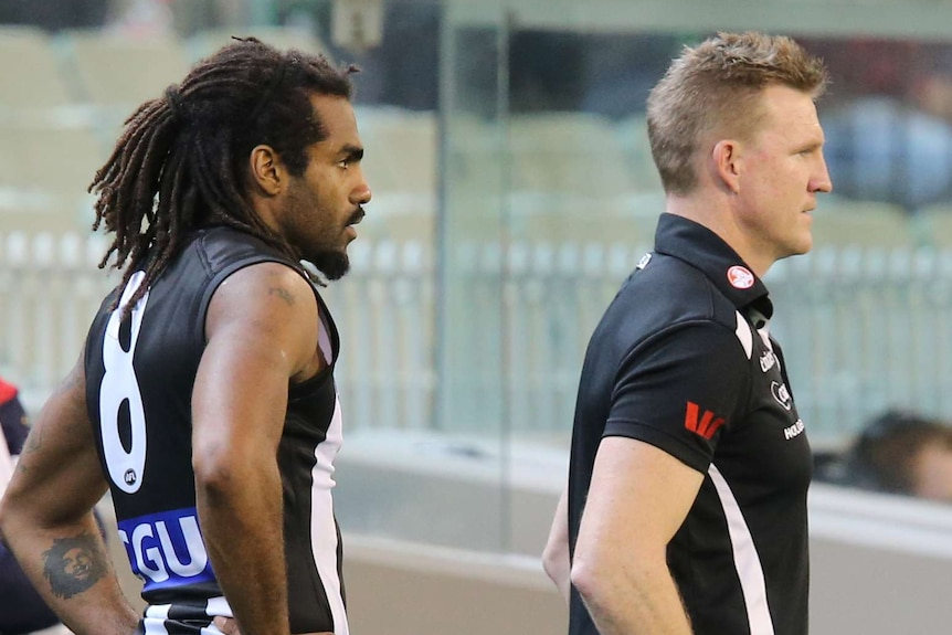 Collingwood coach Nathan Buckley stands in front of Heritier Lumumba on the sideline of an AFL game.