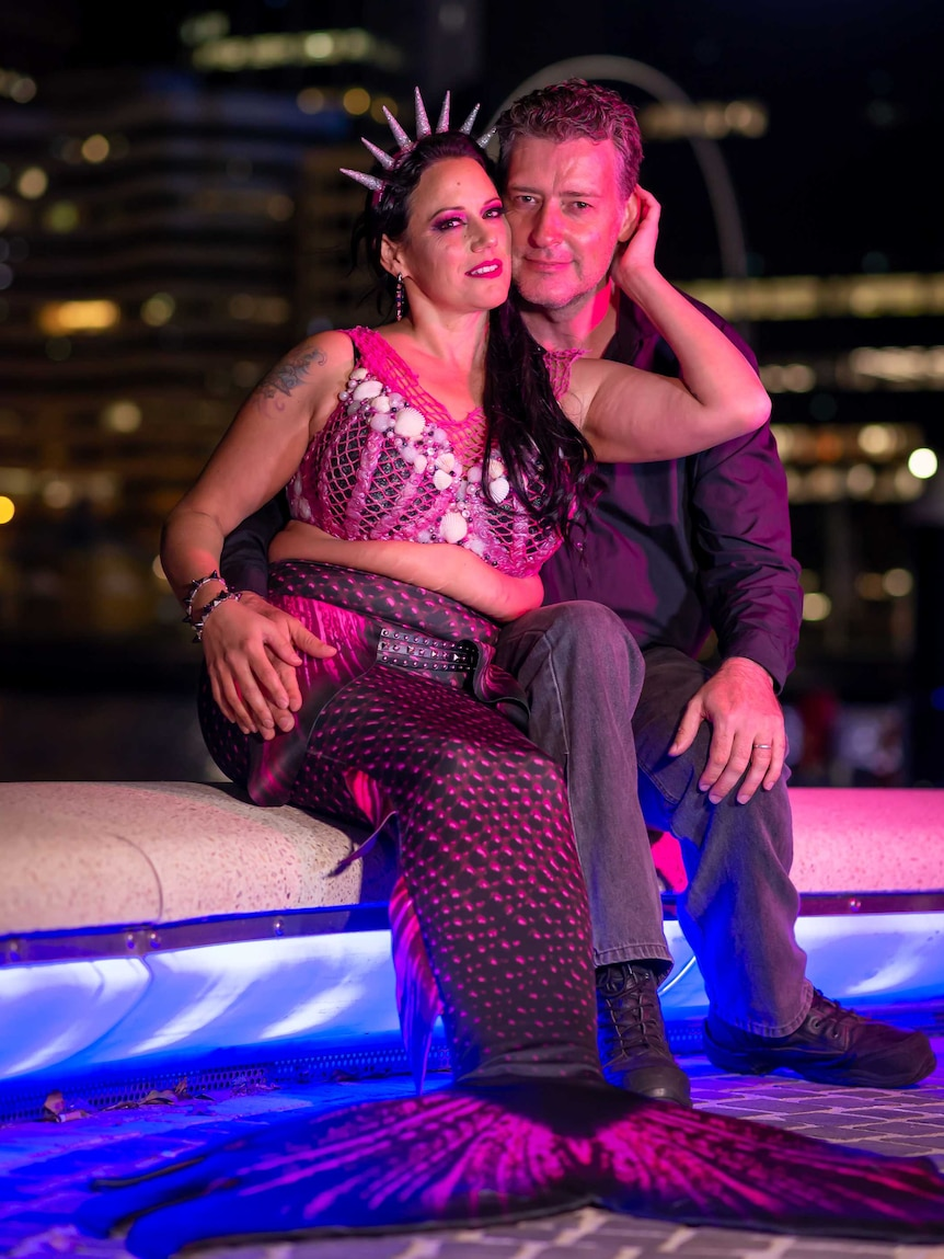 A man and a woman in a tail, sitting near a pool at night.