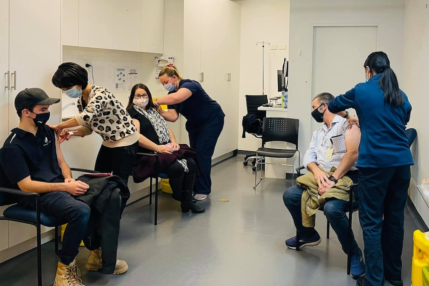 Several patients receive a vaccine at a clinic