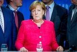 Angela Merkel in a bright fuchsia jacket sits in front of a row of men in suits