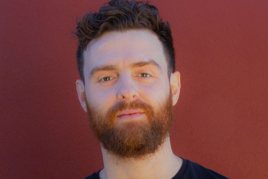 Picture of a man in a black T-shirt against a red background.