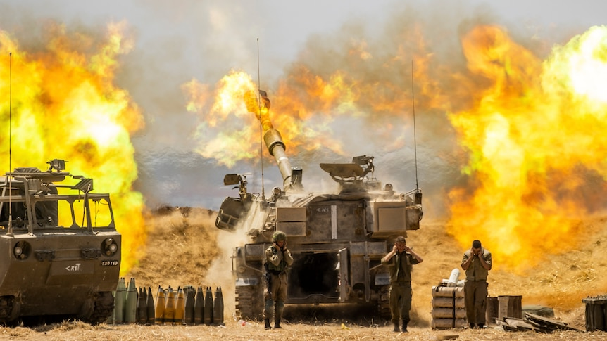 An Israeli artillery unit fires toward targets in Gaza Strip in a burst of flames.