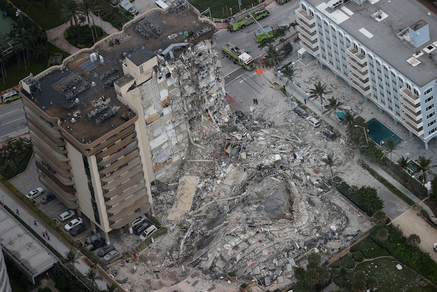 Search and rescue personnel work in the rubble of the 12-story condo tower that crumbled to the ground.