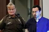 A security guard leads a shackled Larry Nasser into court