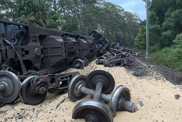 A derailed train lies overturned next to the tracks