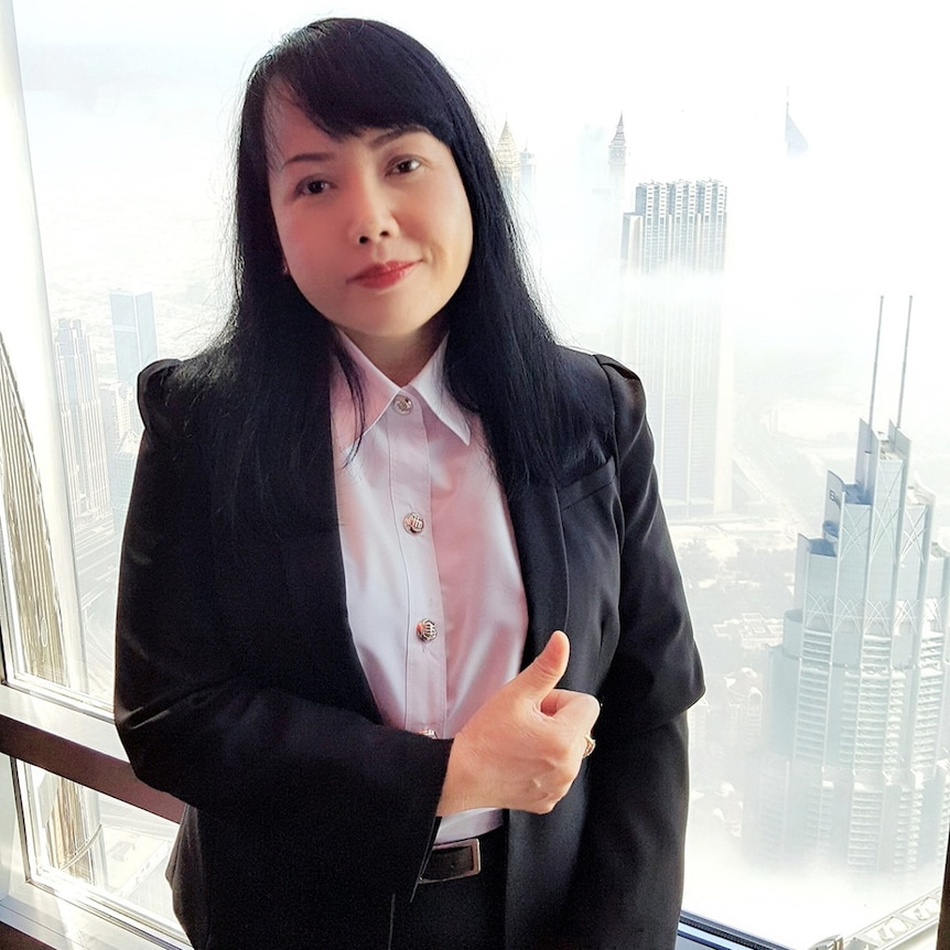 A Thai woman in a suit giving a thumbs up