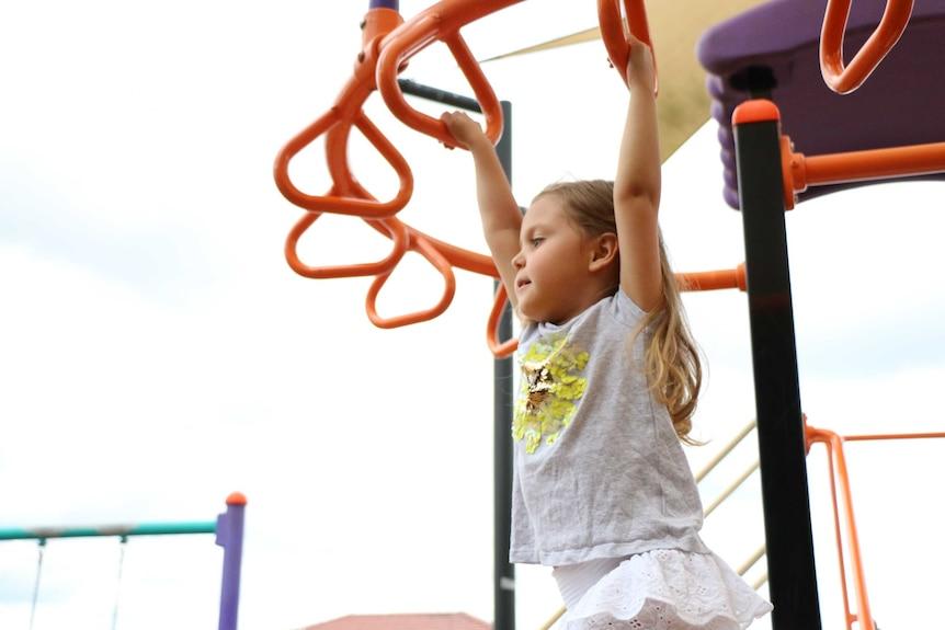 Four year old Eva Garcia swings on the monkey bars