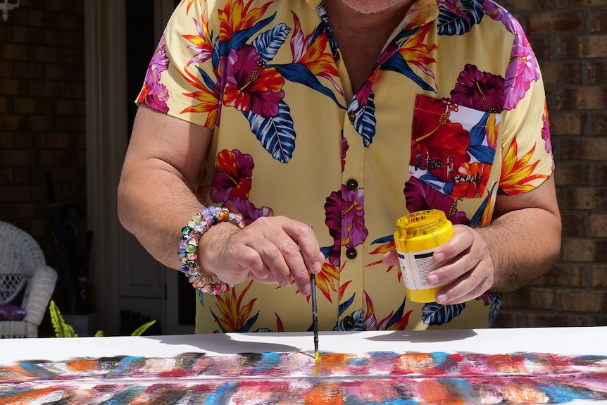A man in a colourful shirt holding a paintbrush