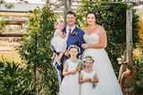 A bride and groom stand in front of greenery with their three young daughters, smiling.
