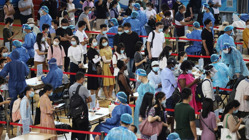 A room full of people in masks or full PPE