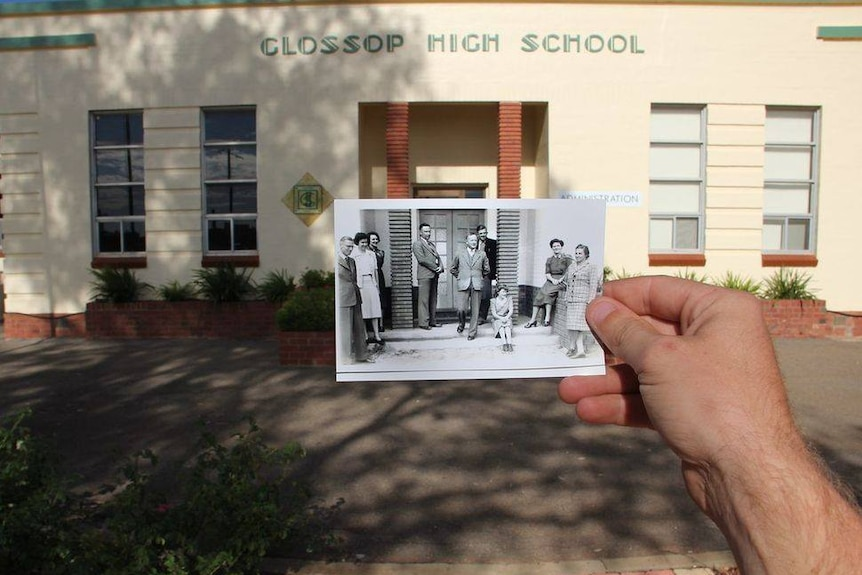 A black and white photo is held in front of a cream building that says Glossop High School.