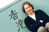 A woman sits next to a green wall with the Chinese characters for Hong Kong painted on it.