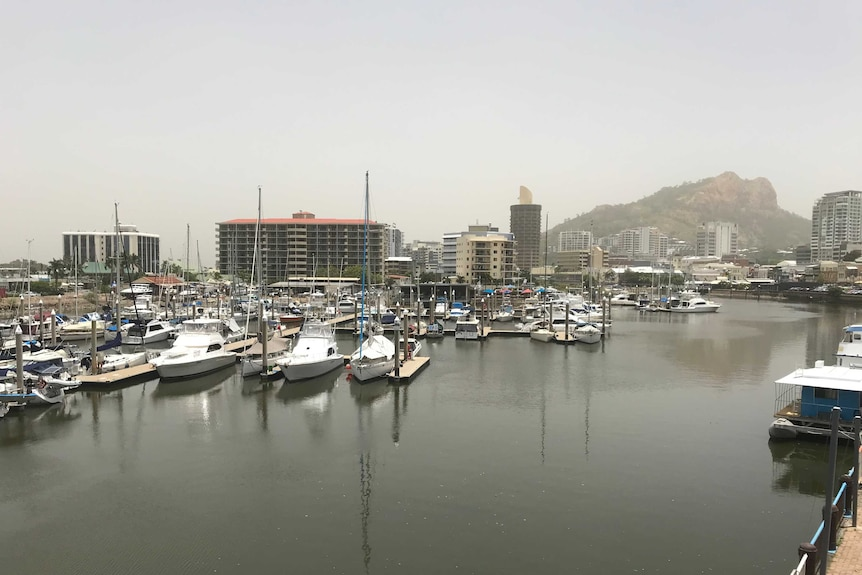 On an overcast day a marine is full of boats and yachts. Hotels, apartment blocks and a rocky mountain are in the background
