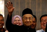 Mahathir Mohamad waves as he is surrounded by people.