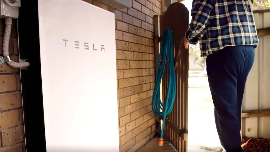 A Tesla battery attached to the outside of a home.