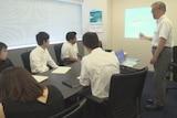 Sakae Kajita teaches younger staff in an office.