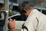 Murray Silvester tries to hide his face from cameras outside the Sale Magistrate Court.