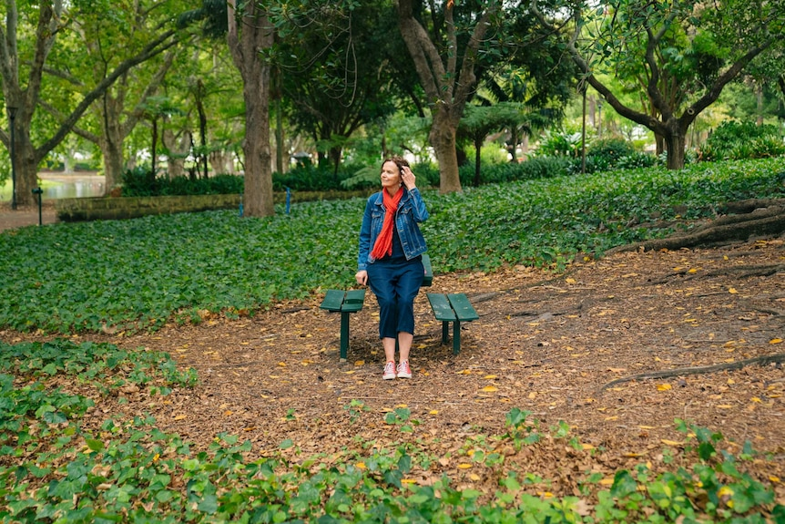 Andrea Hammond sits on a park bench surrounded by greenery.
