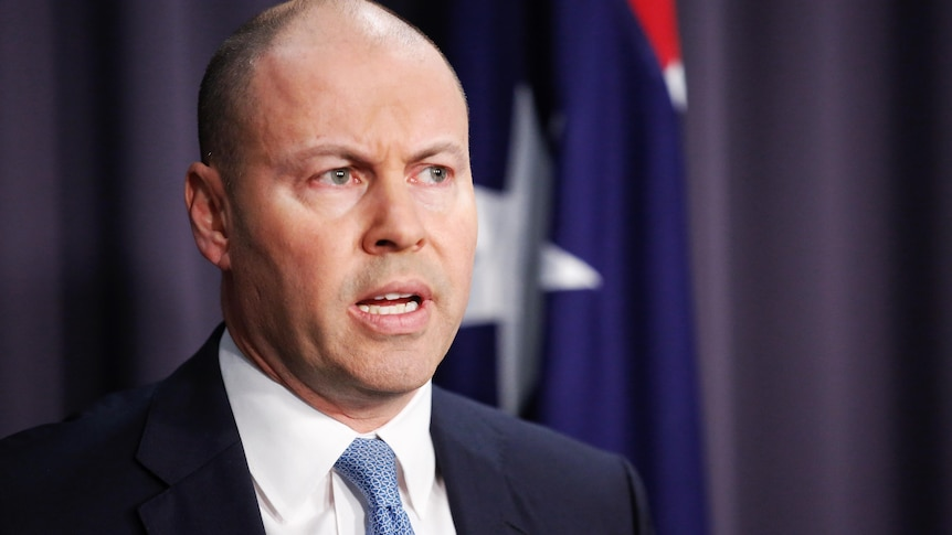 Josh Frydenberg in a suit and tie standing in front of a lecturn in a blue room in front of an australian flag
