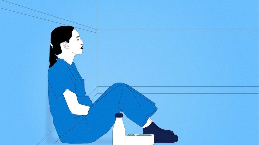 A nurse sits on the ground.