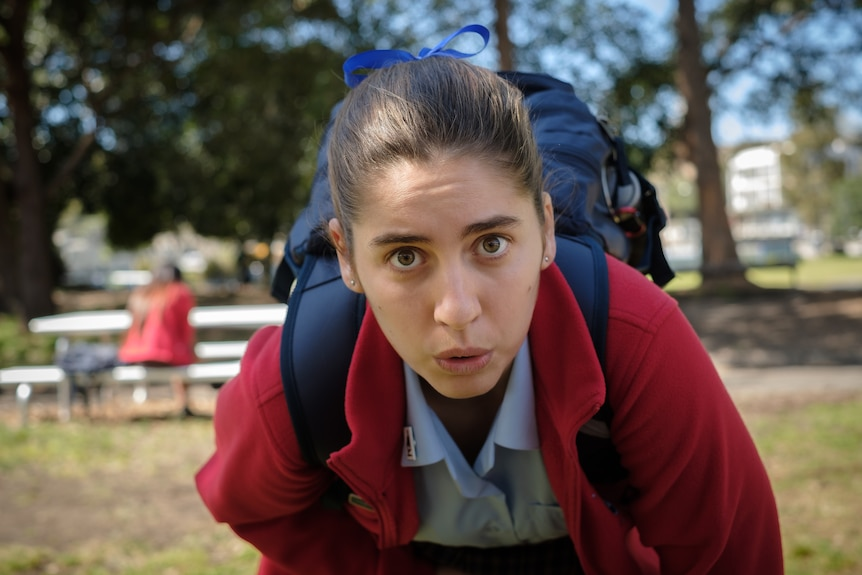 A still from Stan series Bump with a teenage girl in school uniform doubled over in pain