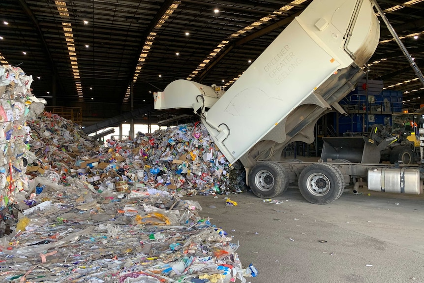 A rubbish truck tips tonnes of recycling into a pile in a warehouse.
