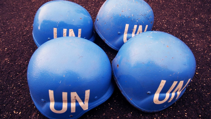 Four blue United Nations helmets sit on the ground.