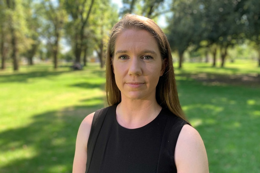 Woman stands in park, looking at the camera