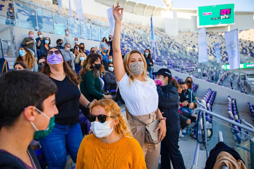 A young woman in a face mask cheering in the stadium surrounded by other people in face masks