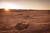 Red sandy earth pictured at sunset with footprints leading into the distance.