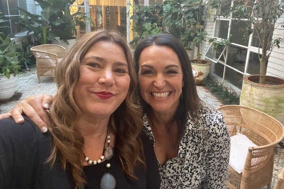 Two women smile at the camera as they take a selfie.