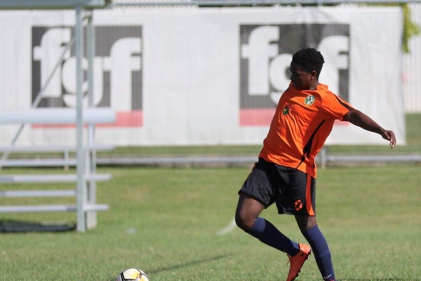 Olivier looks to the ball and kicks it. He wears an orange jersey, black shorts and blue socks.