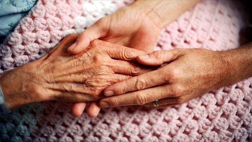 A woman's hand holding an elderly patient