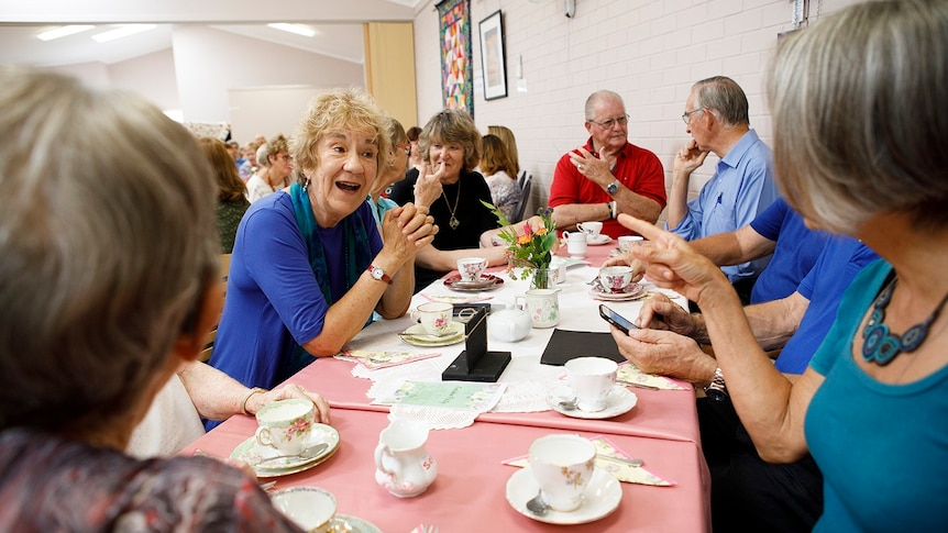 A group of older men and women sit around a table having tea for a story on share housing when retired.