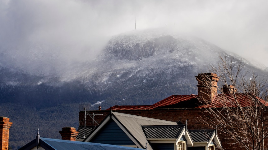 Snow and clouds cover the summit of Mt Wellington.