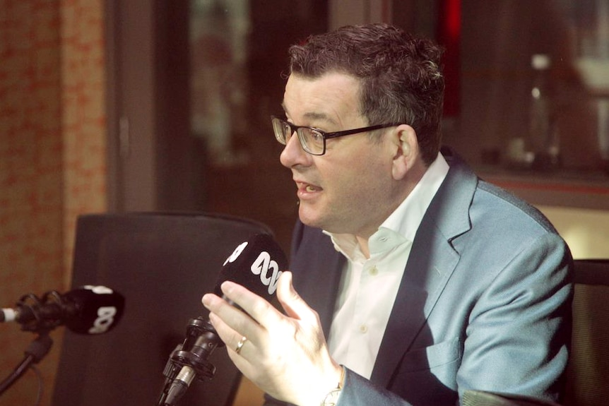 Daniel Andrews, diressed in a suit, sits in front of an ABC-branded microphone.