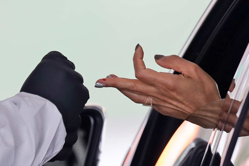 A woman's sticks out from a car window, the middle finger with a patch of blood is extended towards a gloved hand.