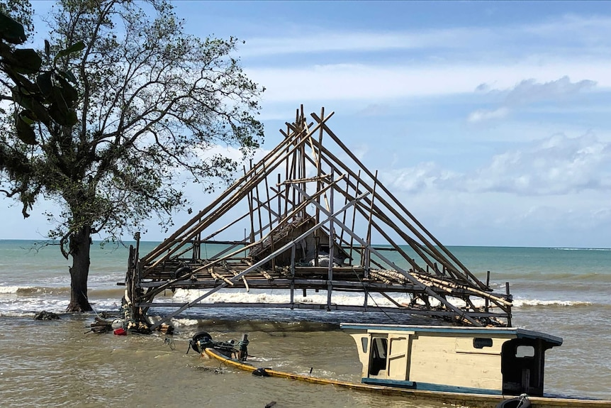 A sunken boat is tied to a pylon in front of an over water shack.