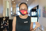 A woman wearing a facemasks with the PNG flag on it shows a card in her left hand and she stands in the lobby of a hotel.