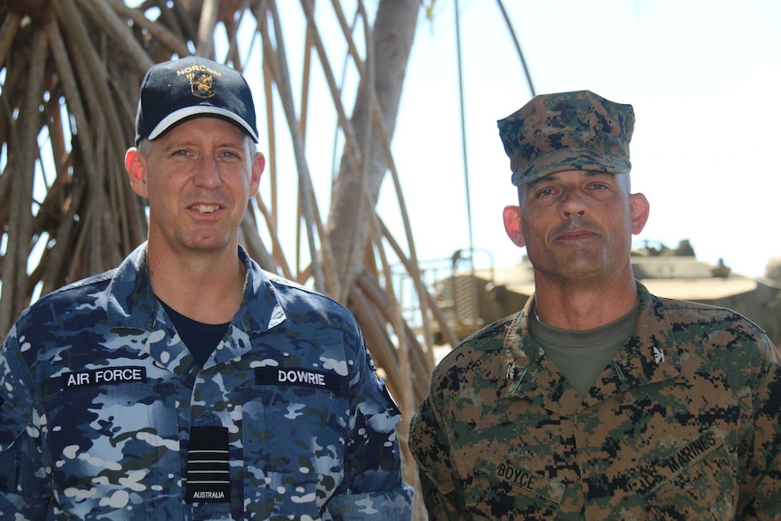 The pair stand in uniform by palm trees