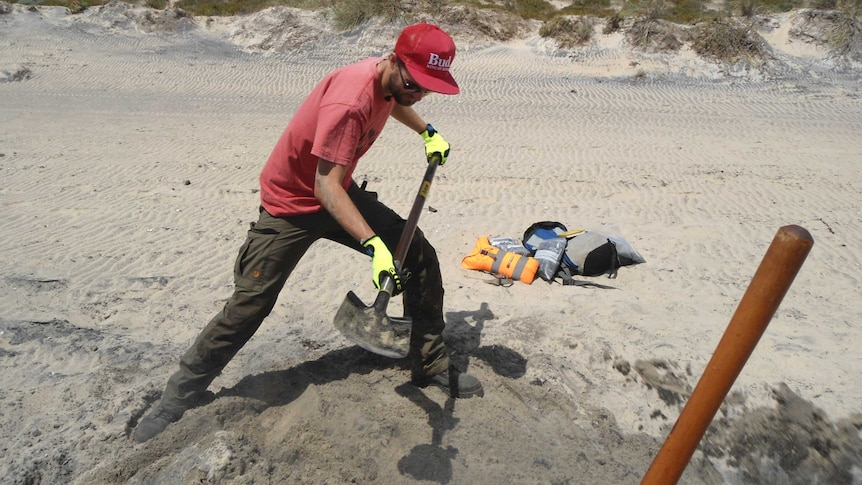 Dr Milo Barham digging for mineral samples on a south coast beach
