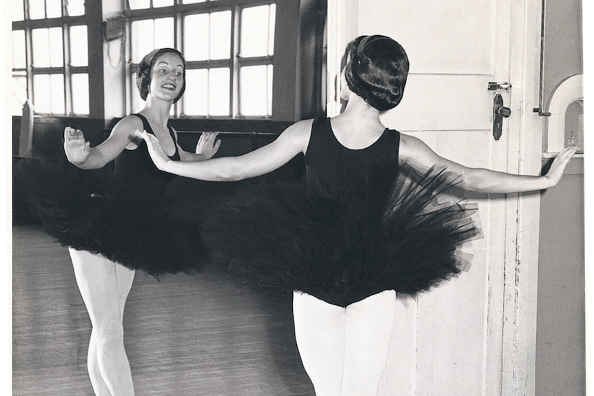 A black and white image of a teenage ballerina looking in mirror wearing tutu