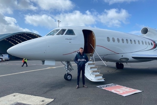 Man standing in front of a charter jet