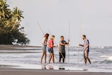 Indigenous tour guide with three guests holding spears at a beach with a rainforest