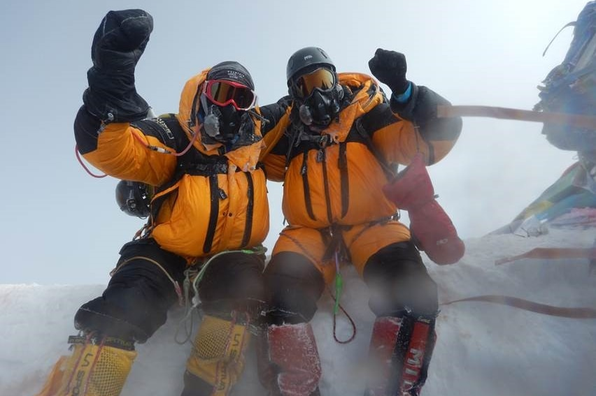 Two men in snow gear jubilant after climbing Mount Everest.